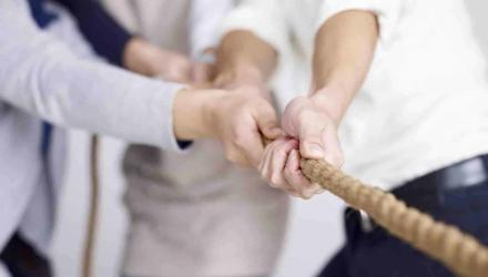 group of businesspeople playing tug-of-war, focus on hands.